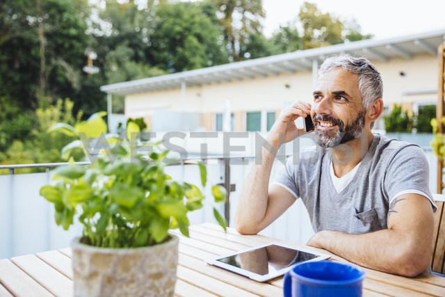 Portrait of man sitting on his balcony telephoning with smartphone - MBEF001227 - Martin Benik/Westend61