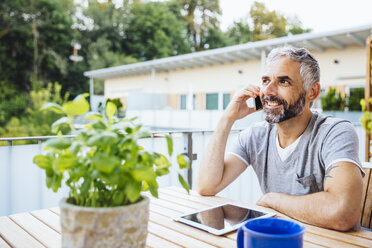 Portrait of man sitting on his balcony telephoning with smartphone - MBEF001227
