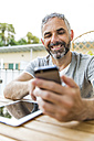 Portrait of smiling man sitting on his balcony with digital tablet using  smartphone - MBEF001122
