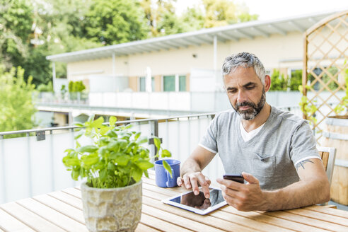 Portrait of man sitting on his balcony using  smartphone and digital tablet - MBEF001229
