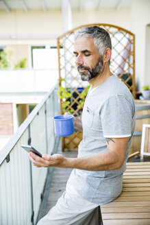 Man on his balcony with smartphone and cup of coffee - MBEF001149