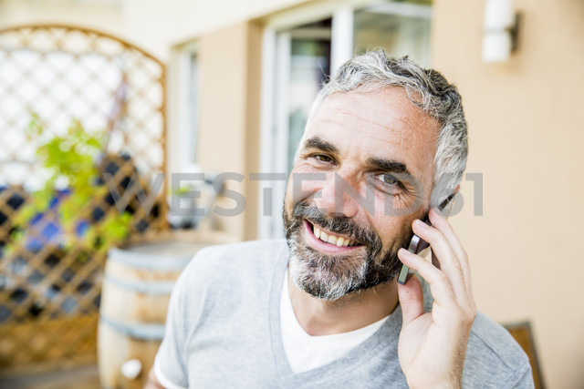 Portrait of man on his balcony telephoning with smartphone - MBEF001157 - Martin Benik/Westend61