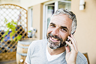 Portrait of man on his balcony telephoning with smartphone - MBEF001157