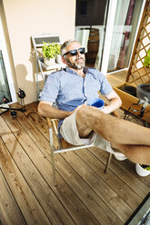 Man wearing sunglasses relaxing on his balcony - MBEF001128