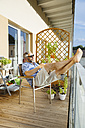 Man wearing sunglasses relaxing on his balcony - MBEF001130