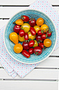 Bowl of different heirloom tomatoes  on cloth and white wood - LVF001863