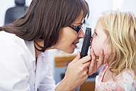 Eye doctor examining girl's vision - ZEF000607
