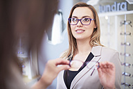Woman at the optician trying on glasses - ZEF000658