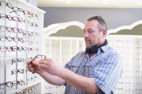 Man at the optician choosing glasses - ZEF000733