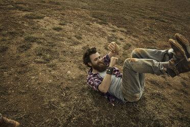 Man with full beard lying on soil - KOF000019