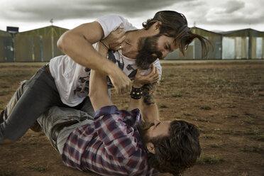 wo men with full beards fighting in abandoned landscape - KOF000027