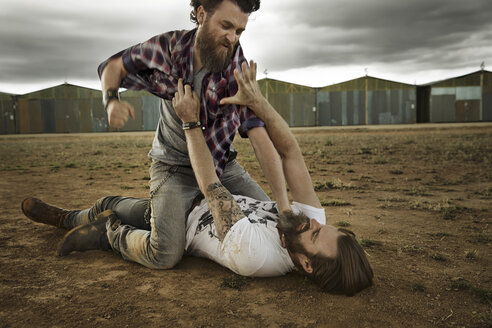 Two men with full beards fighting in abandoned landscape - KOF000029
