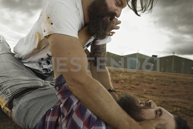 Two men with full beards fighting in abandoned landscape - KOF000031