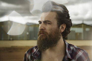 Serious man with full beard in abandoned landscape - KOF000041