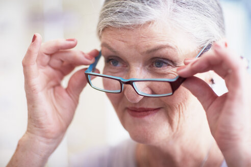 Senior woman at the optician trying on glasses - ZEF000746