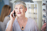 Senior woman at the optician talking on cell phone - ZEF000629