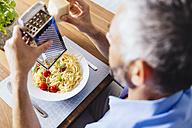 Man grating parmesan on his pasta - MBEF001133