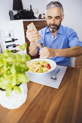 Man flavouring his pasta with pepper - MBEF001135