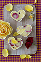 Rose butter and rose petals on chopping board - MYF000549