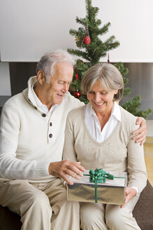 Senior couple exchanging Christmas presents at home - CHAF000191
