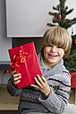 Portrait of happy little boy with Christmas present - CHAF000188