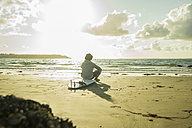 Teenage boy sitting on the beach watching sunset - UUF001703