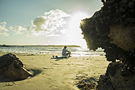 Teenage boy sitting on the beach watching sunset - UUF001704