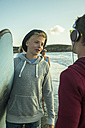 Two teenage boys communicationg on the beach - UUF001709