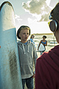 Two teenage boys communicationg on the beach - UUF001710