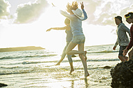 Woman and three teenagers having fun on the beach by sunset - UUF001714