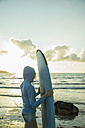 Teenage girl standing on the beach with her surfboard looking at horizon - UUF001723