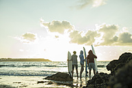 Three teenagers standing on the beach with their surfboards looking at horizon - UUF001725