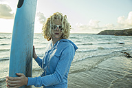 Portrait of teenage girl standing on the beach with her surfboard - UUF001727
