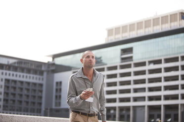 Businessman with smartphone watching something - ZEF000215