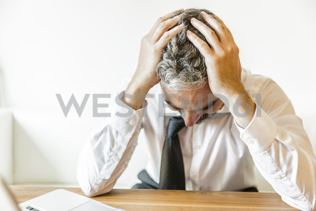 Overstressed businessman with head in his hands - MBEF001153