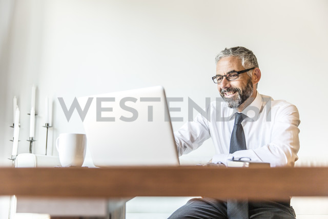 Portrait of smiling businessman working at home office - MBEF001233