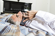 Businessman lying on his bed telephoning with his smartphone - MBEF001222