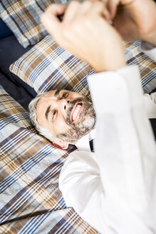 Portrait of happy businessman lying on his bed looking at his smartphone - MBEF001177