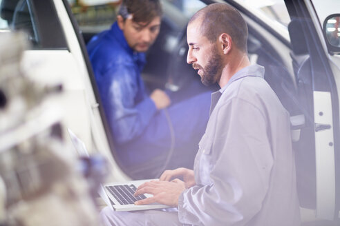 Two car mechanics with laptop in repair garage - ZEF000646