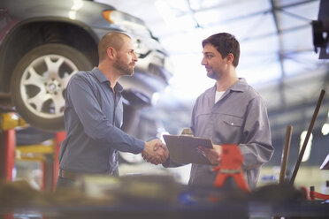 Car mechanic and client shaking hands in repair garage - ZEF000695