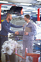 Car mechanic and client shaking hands in repair garage - ZEF000555