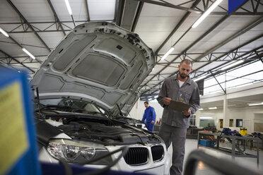 Car mechanic with clipboard in repair garage - ZEF000734