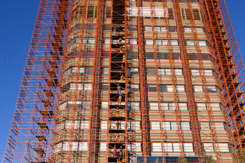 South Africa, Cape Town, row of construction workers standing on scaffolding of high-rise building - ZE000851