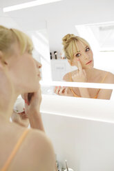 Woman looking at her mirror image while applying face cream - GDF000422