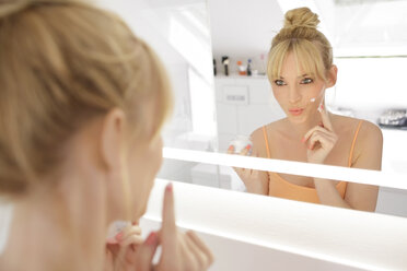Woman looking at her mirror image while applying face cream - GDF000423