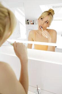 Mirror image of woman brushing her teeth - GDF000427