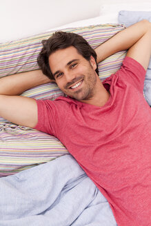 Portrait of smiling young man with hands behind head lying on his bed - JUNF000047