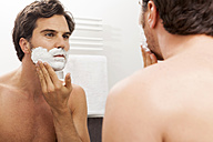 Mirror image of young man applying shaving foam - JUNF000058