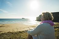 France, Brittany, Camaret-sur-Mer, senior woman sitting at the coast - UUF001779