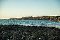 France, Brittany, Camaret-sur-Mer, surfer at the coast - UUF001801